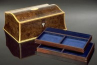 """A double curved jewellery box 13"""" x 9"""" x 5"""". This one is veneered with a fine and subtly figured burr walnut with not too much contrast. The front and lid are decorated with a traditional black and white line. All edges are finished with fine boxwood squares. There is a mother of pearl escutcheon and a central satinwood oval in the lid. The interior is fitted out with two trays in cocobolo and is lined throughout with blue velvet and moiree. It is fitted with good quality brass quadrant hinges and lock and the exterior is french polished."""