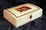 """A domed top jewellery box veneered with figured maple, 10"""" x 8"""" x 4"""" decorated in dyed veneers. The escutcheon is formed from four harlequins - I often do this design with the keyhole cut into the top harlequin. However, for the purposes of balance as this box was relatively low, the escutcheon actually overlaps the lid margin and it made sense on this occasion for the keyhole to be in the bottom one. It is fitted with good quality brass quadrant hinges and lock and the exterior is french polished."""