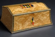 """A double-curved jewellery box veneered with richly figure pale myrtle and decorated with dyed veneers. It measures 13"""" x 9"""" x 5"""" and is french polished."""