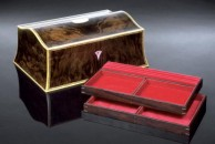 """A double curved jewellery box 13"""" x 9"""" x 5"""" veneered with a dramatically figured burr walnut with plenty of contrast between the sap and the heart wood. The front and lid are book matched and decorated with a traditional black and white line and all edges are finished with fine boxwood squares. There is a mother of pearl escutcheon and a central satinwood oval in the lid. The interior is fitted out with two trays in cocobolo and is lined throughout with red velvet and moiree. It is fitted with good quality brass quadrant hinges and lock and the exterior is french polished. As it happens, this box was stolen. I had sent it to an exhibition of a sort in the Midlands, and they had duly sent it back to me.   Nothing arrived for some considerable time and, despite the fact that the gallery said they had sent it a week or so before nothing continued to arrive. So, I contacted the local sorting office in Willesden and they said that a package fitting the description had been collected a week earlier. By me. Evidently, someone had walked into the postroom at the workshops and picked up a card left in my pigeon hole by the postman telling me there was a parcel at the sorting office. The duty officer had apparently not required any further identification from this person other than their ability to scrawl something that looked vaguely like 'A Crawford' on a card.   The Post Office eventually admitted that they should have required more ID, accepted full liability and paid over the full value of the box. So - you are looking at stolen property. I never saw it again, of course - so, if you see this box, and the riotous walnut is pretty distinctive, don't buy a used car from the owner! And let me know, too."""