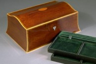 """A double curved jewellery box veneered with some lovely pale old, thick, slightly swirly mahogany veneer. I found this a few years ago and it was difficult to use as it was very dry and crumbly - but its natural colour and figure made it well worth the effort.  The interior features two trays in cocobolo and it is lined throughout with green velvet and moiree. It is 13"""" x 9"""" x 5"""", french polished, and fitted with brass quadrant hinges and lock. The exterior is decorated with a traditional black and white line, boxwood squares, satinwood oval in the lid and a mother of pearl escutcheon."""