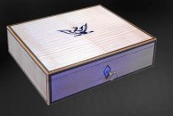 """A box in maple to store and protect six valuable wrist watches. The lid is veneered with bookmatched fidle-back maple with a central detail of the family crest, a griffin. 11"""" x 8"""" x 3"""", danish oiled."""