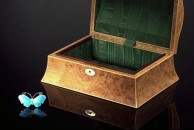 """This is a gorgeous blue enamelled brooch of a blue morpho butterfly that used to belong to my mother, and now belongs to my wife, Hilary. In the background is a small double curved jewellery box 10"""" x 7"""" x 4"""" veneered with burr oak and looking dowdy by comparison. The centre of the lid features a mother of pearl oval which is mirrored by the escutcheon. All edges are finished with fine boxwood squares.  The interior is lined with green moiree and has a fine Cuban mahogany lipping around 3 sides. There is no tray. The lid in hinged using fine brass piano hinge - a method I don't use any more for this format of box, preferring to use quadrant hinges that stop the lid at around 90 degrees."""