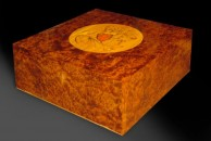 """This sovereign case is veneered with richly figured thuya - unusually coming from the underground root burr of a softwood, the pencil cedar. Although this comes from what is technically a softwood, it is one of the hardest and most brittle of veneers - requiring extreme care to work it neatly. It was particularly challenging on this occasion as there was no inlay around the edges - so it wasn't possible to cover up any chipping of the veneers at the edges.  This case is about 12"""" square, the veneer is book matched and the exterior is French polished."""