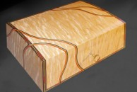 """Domed top jewellery box veneered with quilted maple, 10"""" x 8"""" x 4"""". It is decorated with dyed veneers in the form of a multi-coloured line around the lid and front treated as a single panel and wavy multi-coloured lines cutting across them going over the front, lid and sides. French polished."""