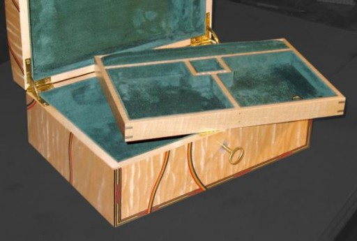 The interior is fitted out with a single tray in ebony and is lined throughout with green velvet and moiree.