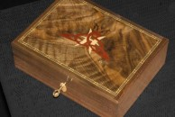 """A simple desk box made from walnut measuring 10 1/2"""" x 8"""" x 4 1/2"""". The lid features a design supplied by the customer and made using dyed veneers. French polished."""