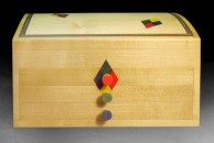 """A domed top box in maple designed to store earrings. It features a multi coloured line around the lid, together with a pair of harlequin details, mirrored on the front. 10"""" x 8"""" x 7"""", french polished."""