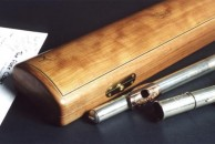 This curved top flute case was made for a beautiful John Lunn flute owned by a keen amateur player. It is in cherry with a simple white/black/white line around the lid. It has John Lunn's logo inlaid on the lid, and in addition there is an inlay of a giant African land snail. Really.